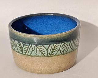 Adorn your home with this stunning little carved planter with lovely green and blue glazes.