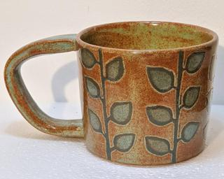 A lovely ceramic mug with a gorgeous carved eucalyptus branch design around the outside and finished with rustic green and blue glazes .
