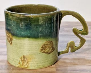 A lovely ceramic mug with little monstera leaves stamped around the outside and unique handle that is quite comfortable to hold.