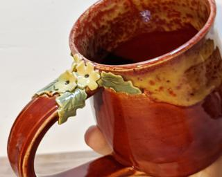 A curvy ceramic mug with a sweet little bunch of flowers on top of the handle.