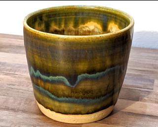 A small olive green and blue cup with an aurora-like glaze pattern on it.