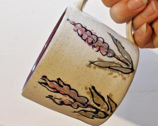 A lovely ceramic mug with lavender flowers painted around the outside.