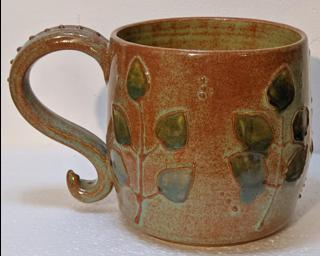 A lovely ceramic mug with a gorgeous textured branch design around the outside and finished with rustic green and blue glazes.