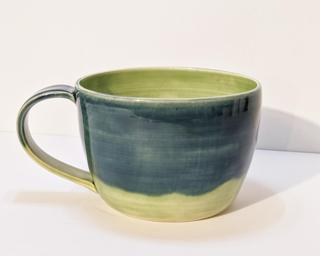 A lovely ceramic mug with lovely combination of blue and green glazes around the outside.