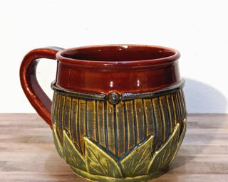 A hefty ceramic mug with a gorgeous color palette around the outside and red on the inside.