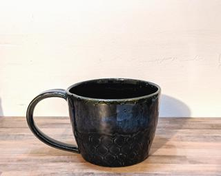 A hefty ceramic mug with a black scale pattern around the outside highlighted with a blue-purple sheen around the top.