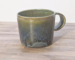 A lovely ceramic mug with unique blend of drippy glazes around the outside.