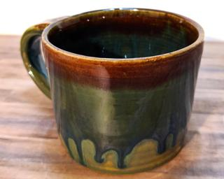 A hefty ceramic mug with a gorgeous  green and blue drip around the outside with a red ring around the top.