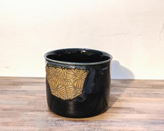 A hefty ceramic mug with a geometric applique attached to the side.