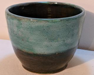 Adorn your home with this one of a kind speckled green and red-brown toned planter.