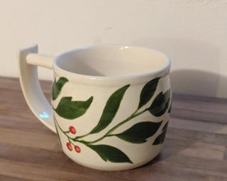 Hand stenciled leaves and berries on a ceramic mug.