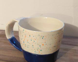 Bright blue and speckled ceramic mug.