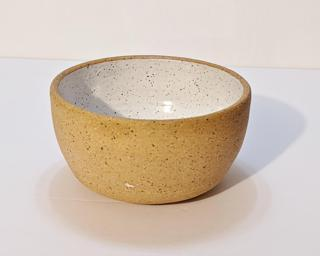 A small handle-less ceramic cup with a white glaze over a mid-fire speckled clay.