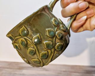 A lovely ceramic mug with ivy vines wrapped around the outside.