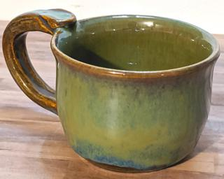 A hefty ceramic mug with a gorgeous sea green and blue drip around the outside.