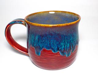 A hefty ceramic mug with a gorgeous drippy blue glaze over a textured red base on the outside and a blue interior.