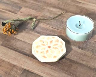 A tiny tealight candle holder/coaster to protect your table.