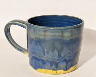 A hefty ceramic mug with a gorgeous wavy blue drip around the outside with a bright blue on the inside.