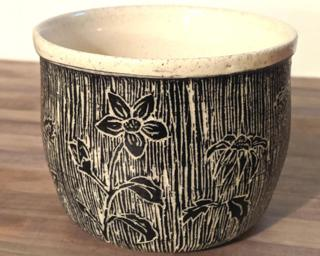 Accessorize your home with this hand carved ceramic planter with a unique floral design.