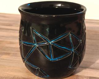 Decorate your home with this hand carved ceramic planter with a unique geometric design.