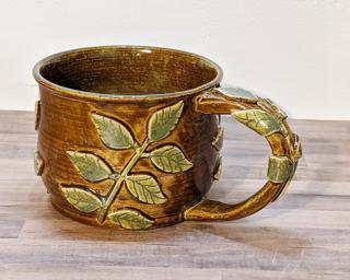 A lovely ceramic mug with leaf sprigs around the outside and on the handle.