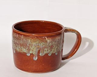 A hefty ceramic mug with a gorgeous red and blue drip around the outside with a red and yellow on the inside.