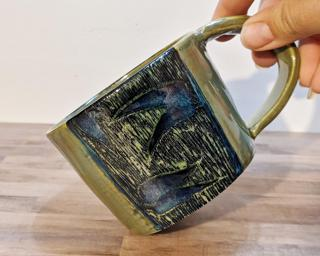 A lovely ceramic mug with carved bamboo around the outside.
