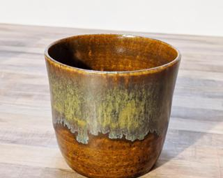 A small ceramic cup with cascading glazes around the outside.