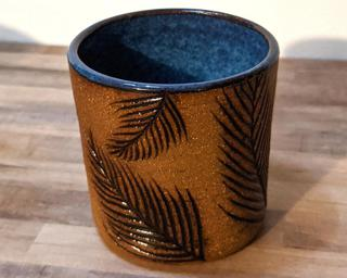 A small ceramic cup with carved pine leaves around the outside and a lovely mottled blue on the inside.