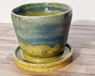 Adorn your home with this one of a kind speckled ceramic planter, complete with a drain hole on the side and a small attached dish to catch any water overflow.