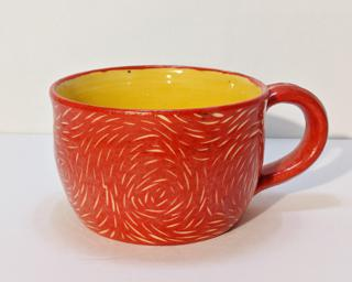 A brightly colored ceramic mug, perfect for a morning cup of coffee.