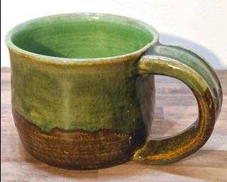 A hefty ceramic mug with a gorgeous olive green drip around the outside.
