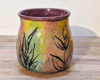 A very colorful ceramic mug with leaf designs painted around the outside.